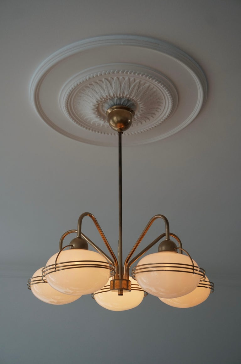 One Italian chandelier in brass with five white blown glass globes.  Measures: Diameter 53 cm Height 65 cm. The light requires five single E14 screw fit lightbulbs (40Watt max.) LED compatible.