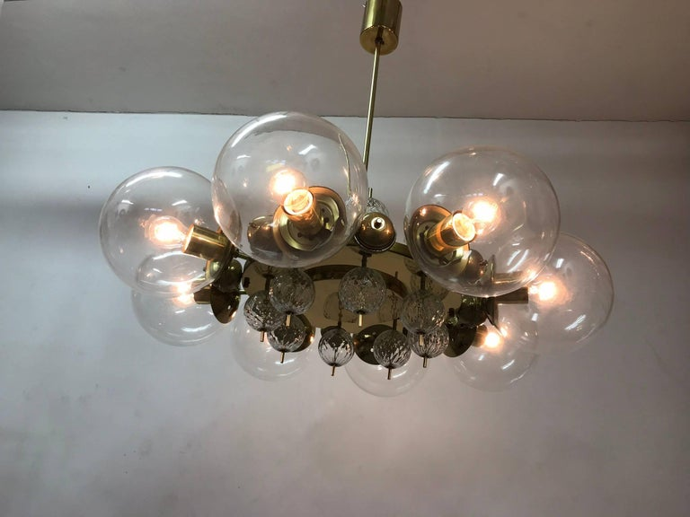 An unique chandelier from the 1965s. The brass construction is completed with the original patina. The glass balls are hand-blown. The conditions is very nice. The chandelier is fitted with eight glass spheres of 20 cm in diameter. Each arm has an