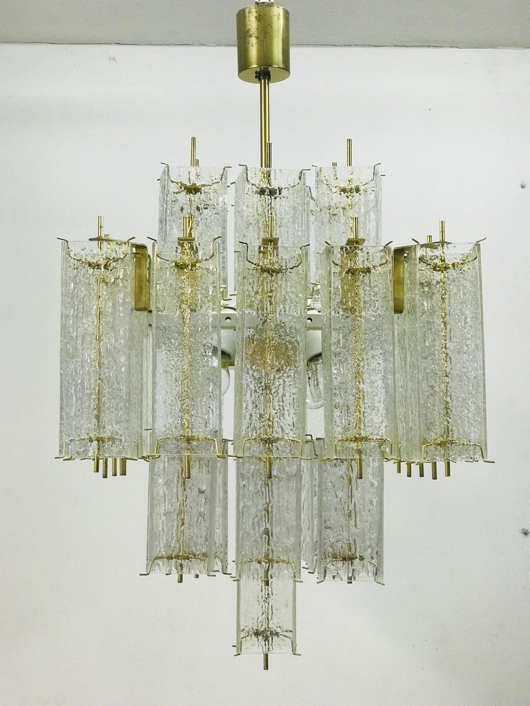 Chandelier is consisted of glass cubes (4 pieces of spare glass) and metal construction with brass fasteners. The chandelier makes a timeless body of modern times.