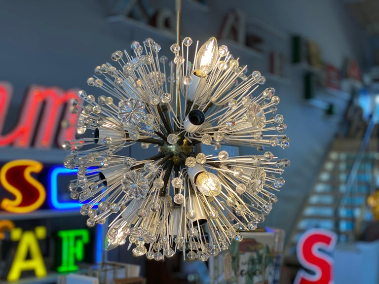 This enchanting chandelier was designed by Emil Stejnar in the 1950s for the Viennese lighting manufacturer Rupert Nikoll. Stejnar's ceiling lamps are characterized by star shapes and delicate glass lacquer. This specimen, the Sputnik lamp, is