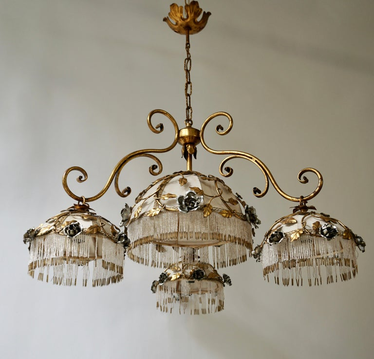 Chandelier with brass leaves and silver colored roses.
