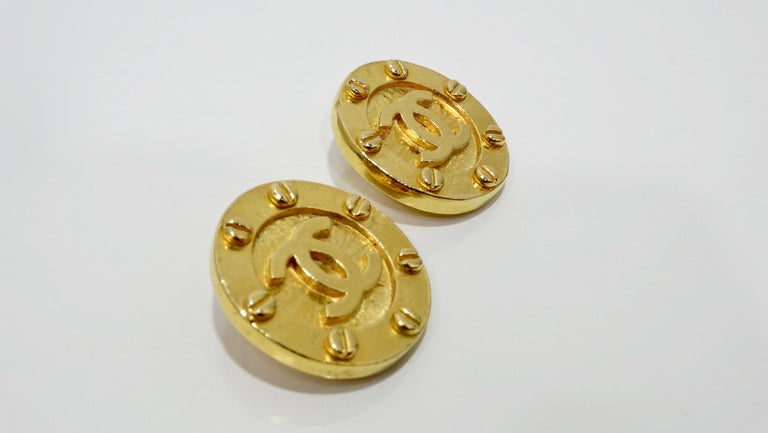 Keep it classic with these Chanel earrings! Circa 1980s, these large medallion earrings are gold plated and feature the iconic CC in the center with unique screw head details around the trim. Chic and timeless, these earrings will pair perfectly