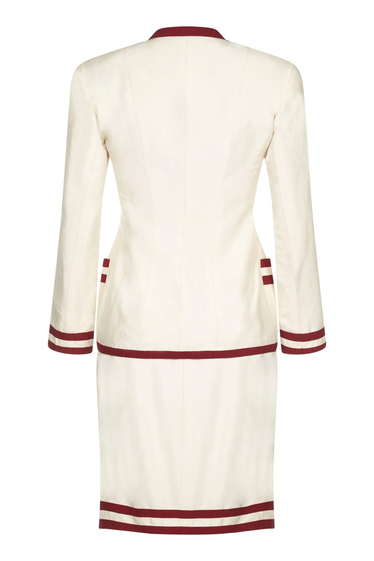 This smart early to mid 1990s Chanel cream silk 2-piece suit with grosgrain ribbon trim is in exceptional condition and perfectly exemplifies the casual chic synonymous with this classic and celebrated brand. The 100% raw silk outer of the jacket is