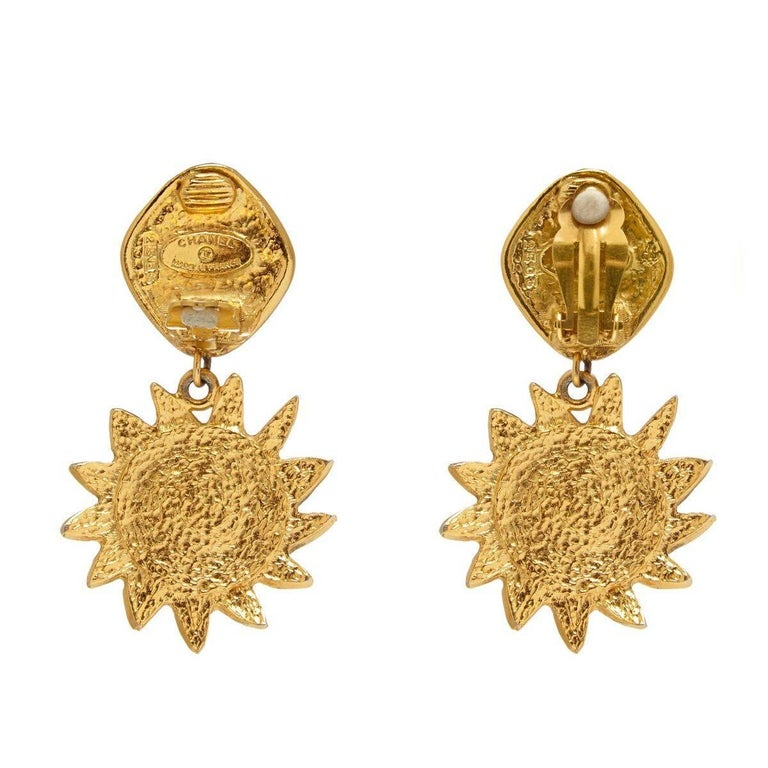 Charming Chanel 1990s gold tone sun drop earrings with pearl inset and abstract flower motif clip fastening. The designers signature is located on the reverse of each piece below the clip. In very good vintage condition, just a pin dot on the pearl