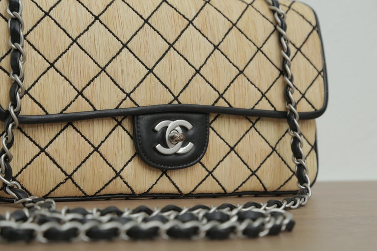 Exterior scuffs or marks Some tarnishing on the turn lock hardware  Description: Tan quilted raffia Chanel Classic single flap bag with silver tone hardware, black leather trim, single chain link shoulder strap, black leather lining, dual pockets at