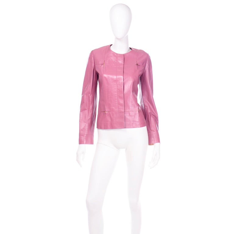This berry pink leather Chanel jacket is in a soft lambskin leather and it has pops of rose gold in fun square star cutouts. This unique detail is found along the front of the jacket and on the cuffs of the sleeves. This jacket is collarless and has