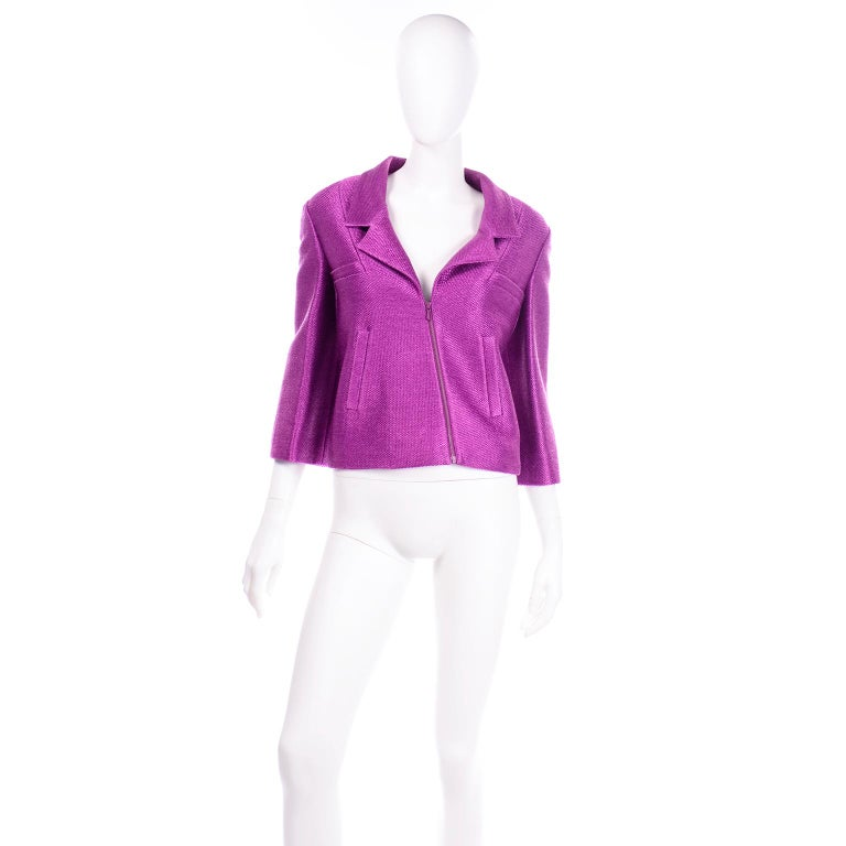 This incredible S/S 2001 vintage Chanel jacket is made from a woven magenta purple cotton blend fabric with a metallic sheen. The jacket and sleeves are slightly cropped and there is a front zipper that is asymmetrical on the bodice. The jacket has