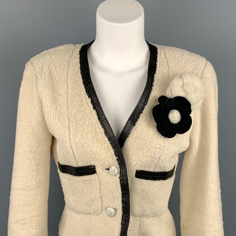 CHANEL 2003 jacket comes in a cream shearling with a black leather trim featuring two camelia pins, front pockets, and a two button closure. Made in France.  Very Good Pre-Owned Condition. Marked: FR 38  Measurements:  Shoulder: 16.5 in. Bust: 34