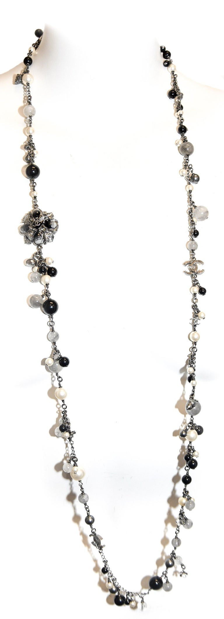 Instantly recognizable as an iconic Chanel necklace!  Pearls,  Onyx, Hematite and rutlilated quartz beads are only the beginning! Ever familiar Camellia is adorned on each side with CC logo.  Bezel set crystals, acorns, CC logos and tiny flower