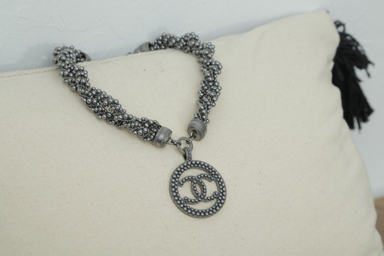 Chanel grey beaded crystal CC chain choker with CC medallion pendant. This bold choker necklaces features multiple strands of faux dark pearls braided together. There is a large CC pendant at the front center and a smallCC dangling charm at the