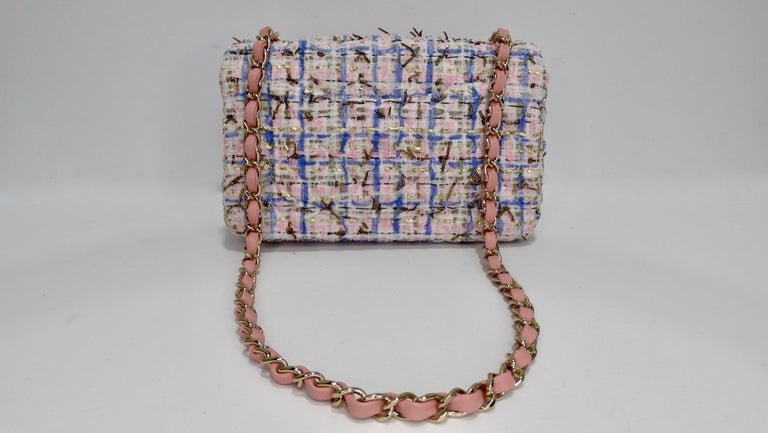 Add this adorable Chanel to your collection! Circa 2019 from their Cruise collection, this chic mini flap bag is crafted from pink, blue, gold and metallic gold tweed fabric with Chanel's signature quilted stitching. The bag features light gold