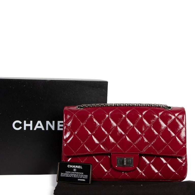 Excellent condition  Chanel 2.55 Reissue 227 Cranberry Patent Leather Bag  This gorgeous Chanel Reissue features the classic double flap design in exclusive cranberry red patent leather, finished with a dark grey chain strap and the iconic front