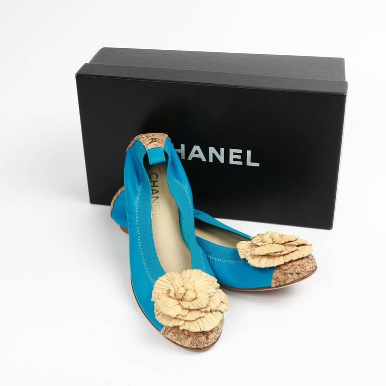 New in the box, lovely pair of Chanel Ballerina, adorned with a stylized camelia made of raffia. In two tones color, turquoise and beige, those shoes are making the difference with its cork front and back adorned with the  iconic CC symbol.  In