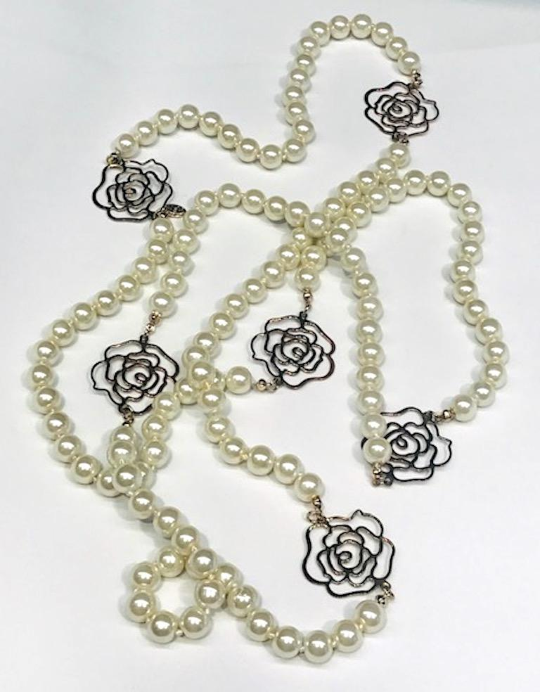 From the Chanel Autumn 2012 collection is this 63 inch long faux pearl necklace with 6 Chanel camelia cutout flowers. The faux pearls are individually knotted and and 10 mm 3/8