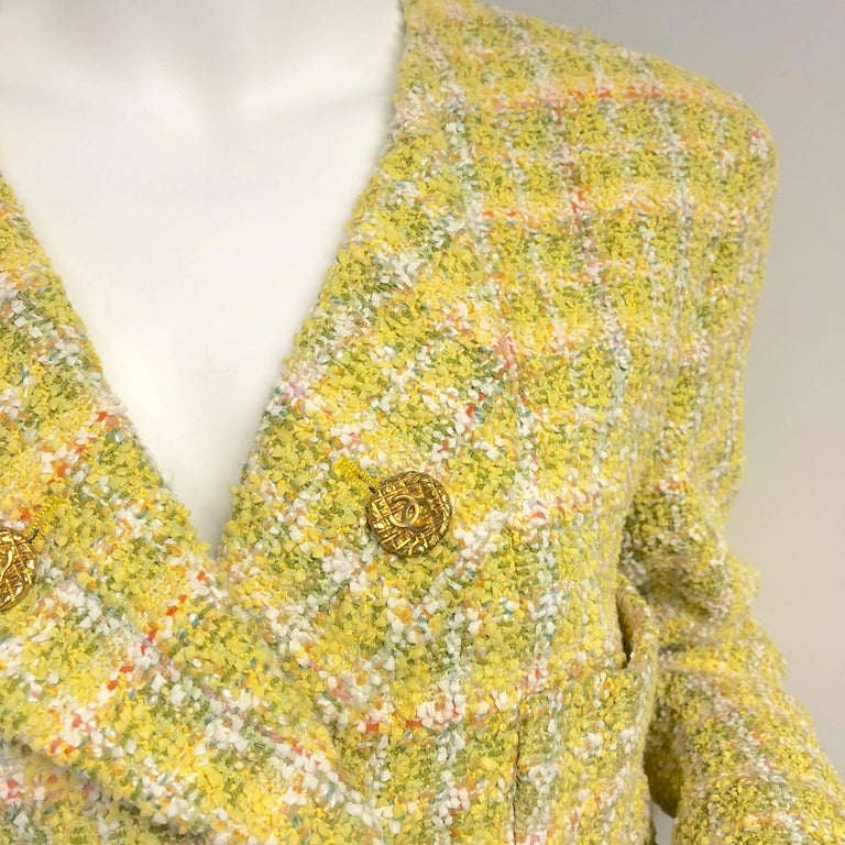 Vintage CHANEL yellow fantasy jacket with double breast and 5 gold quilted effect logo embossed buttons. Tweed has hints of mustard, chartreuse, pink and orange. 4 patch pockets in front. Each cuff has 3 working buttons. Signature CC embossed lining
