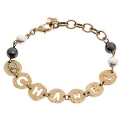 Chanel Aged Gold Tone Cutwork Logo Charm Beaded Bracelet
