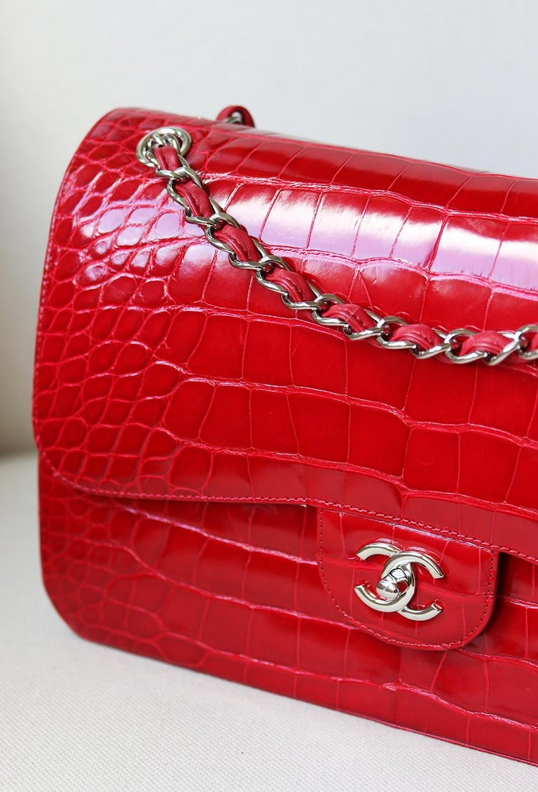 Chanel Alligator Jumbo Classic Double Flap Bag has been hand-finished by skilled artisans in the label's workshop. Boasting vibrant red alligator leather exterior, this design is accented with silver-toned and red lambskin-leather chain strap. Made