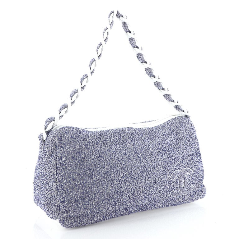 This Chanel Beach Resin Chain Hobo Terry Cloth Large, crafted in blue terry cloth, features woven-in fabric resin chain-link strap and CC logo. Its zip closure opens to a white fabric interior.  Estimated Retail Price: $1,700 Condition: Great. Minor