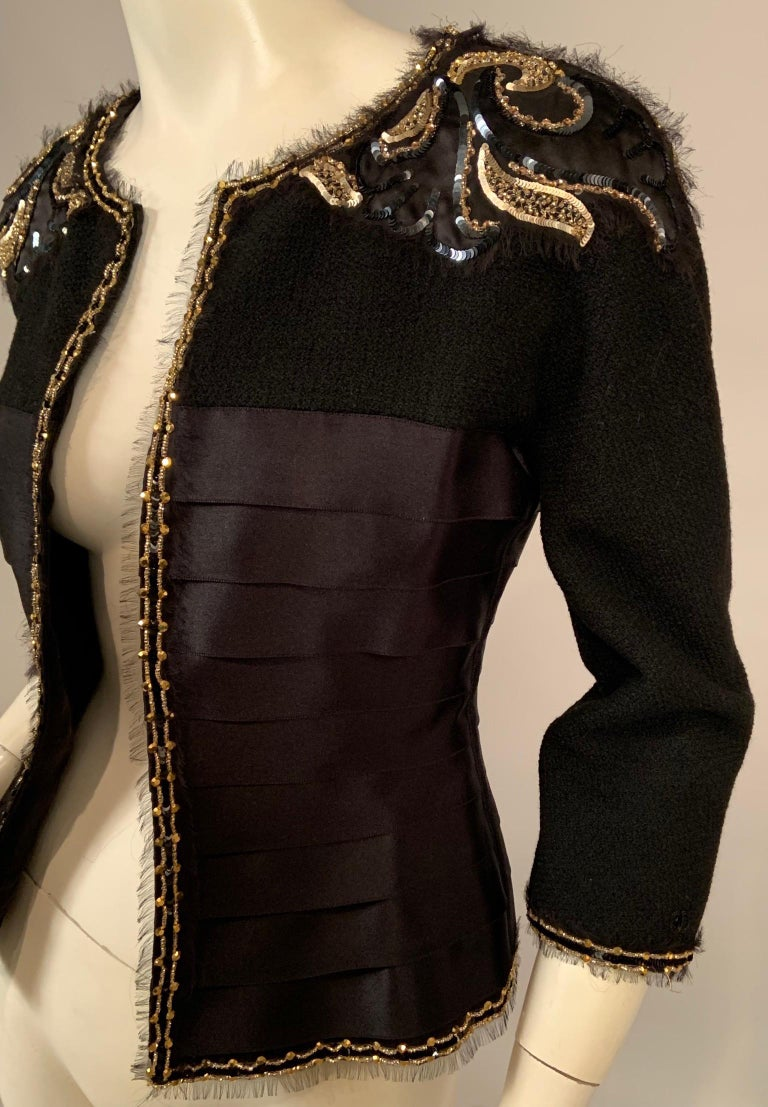 This is a jewel of a Chanel jacket, gorgeous over an evening gown and very chic with black pants or skirt. The jacket has a black wool boucle yoke and sleeves. The shoulders are appliqued with black satin that is embellished with black and gold