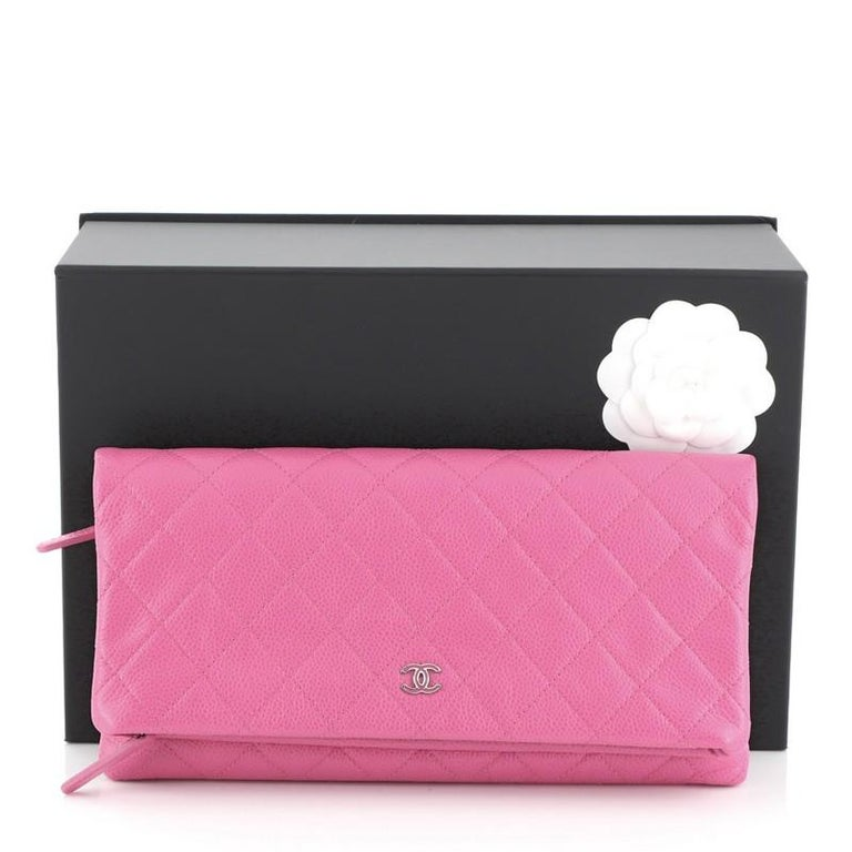 This Chanel Beauty CC Clutch Quilted Caviar, crafted in pink quilted caviar leather, features a folded flap with mini CC logo at the front and silver-tone hardware. Its zip closure opens to a pink fabric interior with zip pocket. Hologram sticker