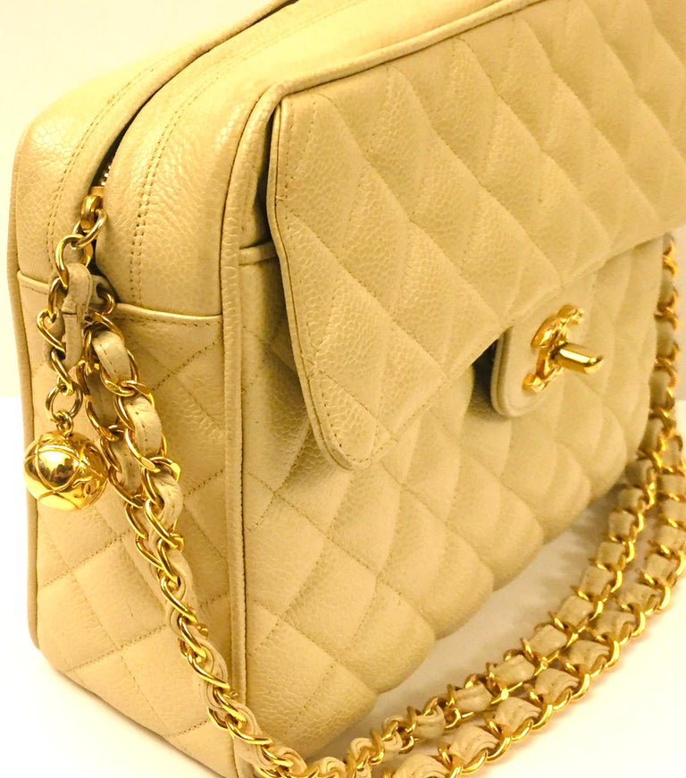 """- Vintage 90s Chanel beige caviar double chain handbag.   - Gold toned """"CC"""" ball zip closure and front pocket with turn lock.   - Compartments interior and zip closure.   - Measurements: 26cm x 20cm x 8cm. Drop: 24cm"""