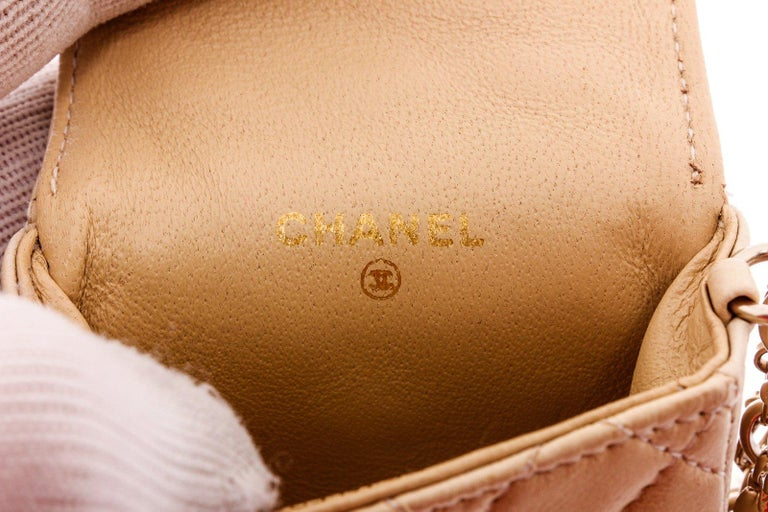 Beige Quilted leather Chanel CC Mademoiselle mini pouch bag charm with gold-tone hardware, tonal leather lining, gold-tone hardware, signature charms with round key ring and overall flap with button snap closure.  20550MSC