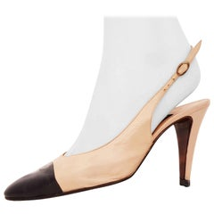 Chanel Beige Leather Heels with Black tip and small belt behind.