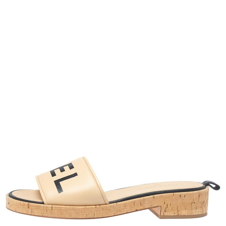 For days of ease and style, Chanel created these pretty slides. They have uppers crafted from quality leather and detailed with 'CHANEL', low heels and insoles lined with leather for comfort. The beige-hued cork slides will come in handy with many
