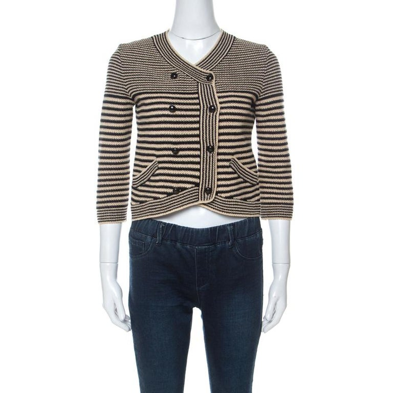 This sophisticated creation from the house of Chanel comes in lovely hues of black and beige. It has been knitted meticulously from a silk blend. This short cardigan features several details that add to the stylish silhouette. With its black