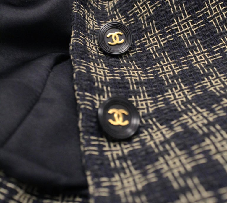Chanel black and gold tone check cropped jacket with notch collar.  This jacket is accentuated with ornate CC buttons for front closure.  Four front patch pockets decorate this blazer.     With structured shoulders and marked waistline, this cropped