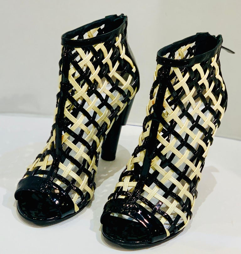 Hard to find size 11 or 41, Chanel Black and White Patent Leather Cage Peep Toe Booties Shoes from the Spring 2015 runway collection of the legendary luxury brand Chanel. These edgy, ankle high booties feature glossy patent leather in white and