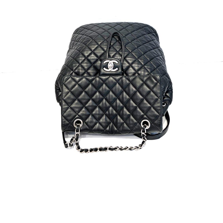 This Chanel  Backpack Quilted Lambskin Large, crafted in black quilted lambskin, features a frontal flap, woven-in leather chain top handle, flat leather backpack straps, and silver-tone hardware. Its turn-lock and drawstring closure opens to a