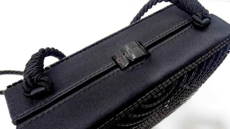 Complete your evening look with this stunning Chanel bag! Circa 1997-1999, this boxy evening bag is crafted from black satin and features a black beaded motif on both sides, a black rope shoulder strap, and a Chanel embossed top closure. Interior is
