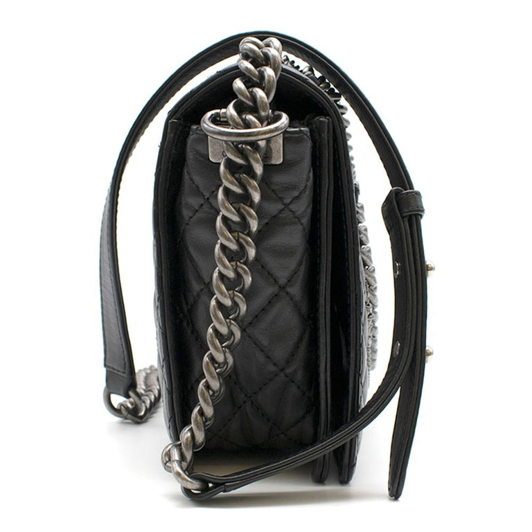 Chanel Black Caviar Leather Boy Bag with chain details.   - Palladium hardware - Chain details  - Black grained leather body - CC mademoiselle lock - Chain strap can be worn on the shoulder or across the body - Dust Bag Included   Please note, these
