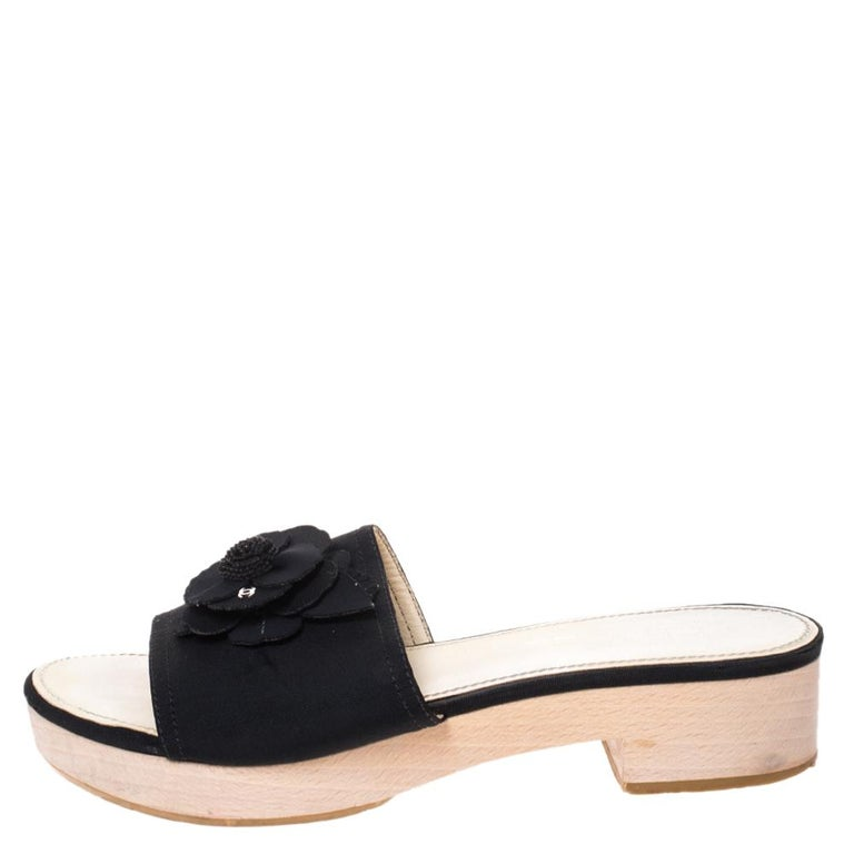 These sandals from the house of Chanel are a fine blend of comfort and class. They are designed from luxurious canvas for maximum comfort and come in a classic black color. They are adorned with the signature camellia flower on the uppers and also