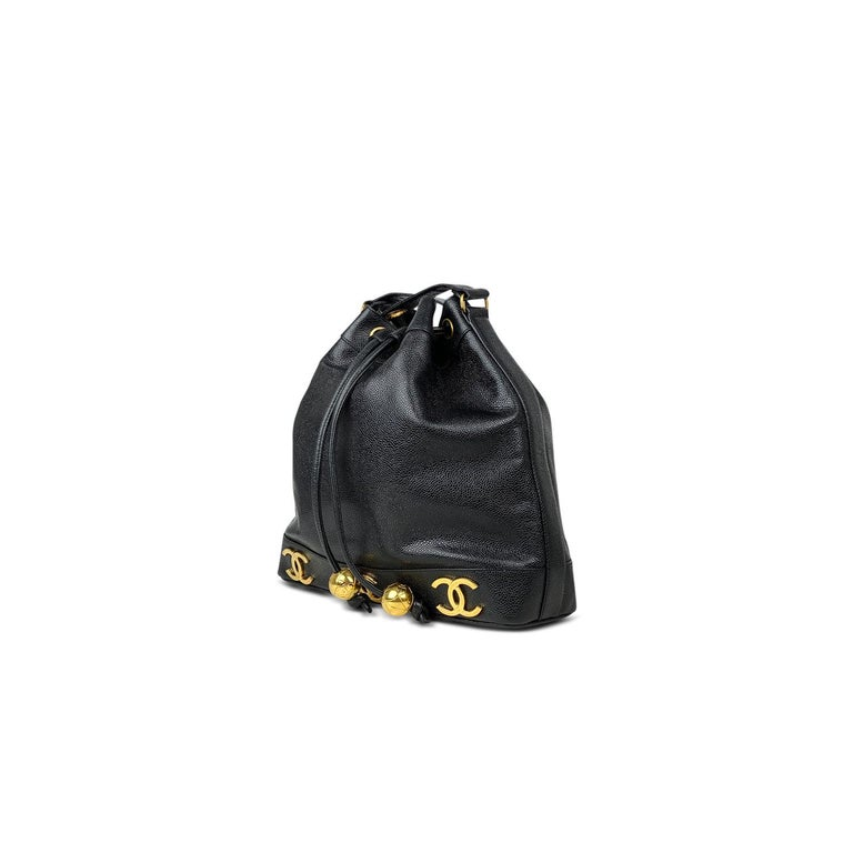 Black Caviar leather Chanel bucket bag with  - Gold-tone hardware - Dual chain-link and leather shoulder strap - CC logo adornments at exterior - Tonal leather interior and drawstring closure at front flap featuring round logo adornments  Overall