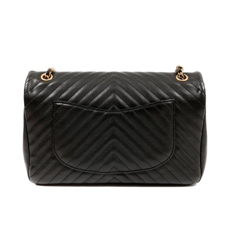 This authentic Chanel Black Chevron Calfskin Rock The Corner Flap Bag is in excellent condition.  An edgy sister to the classic flap style, it is updated with quilted gold metal accents and chevron quilting. Gold tone quilted texture double cc twist