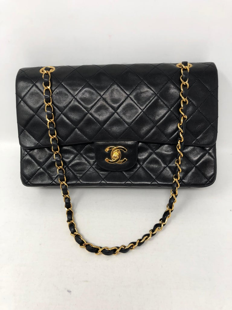 Chanel Black Classic Double Flap in medium size. Black lambskin leather with gold hardware. Burgundy interior. Double flap classic. Iconic classic never goes out of style. This one is in great vintage condition. Can be worn doubled or longer with
