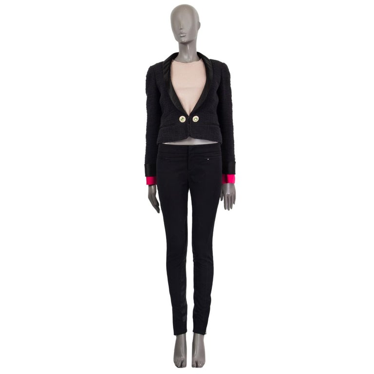 Chanel tweed dinner jacket in black cotton (100%) with satin shawl collar and cuffs. Detachable hot pink silk cuffs, rhinestone and faux pearl embellished buttons, slit pockets (still sewn shut. Closes with a hidden hook on the front. Lined in silk
