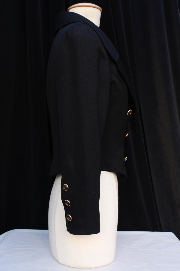 CHANEL BOUTIQUE – Elegant short jacket composed of black cotton blend, with long sleeves and tailored collar. It closes with a double series of gilded metal and black resin buttons with gilded metal CC logo. Black monogrammed silk lining.  No