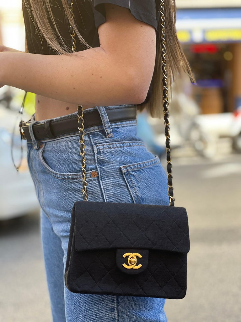 Chanel Mini Flap made of black fabric with golden hardware. Closure with CC hook, internally not very large. Equipped with a leather and chain shoulder strap. It seems in perfect conditions.