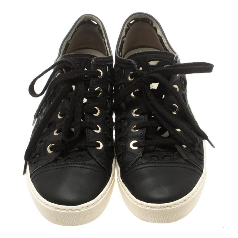 Experience high-end fashion and effortless comfort with these sneakers by Chanel! The exterior material features leather, fabric and exemplary flower cut out design in black. These lace-up sneakers are coupled with silver-tone hardware eyelets. They