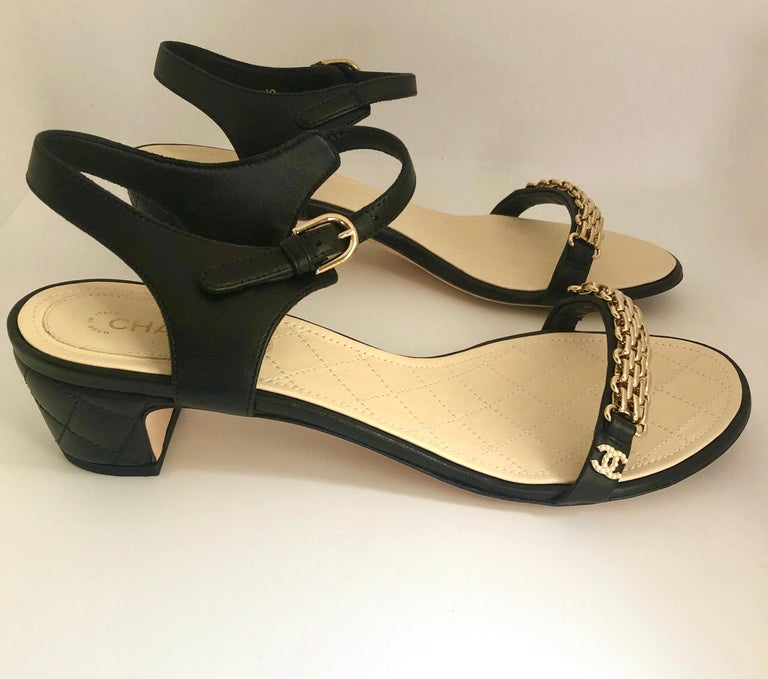Offered is a pair of black Chanel signature quilted leather gold metal chain over leather strap sandal with 2