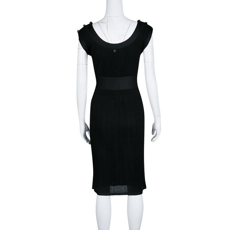 It is a classic black dress from Chanel that is cut to a slim silhouette. Ideal for parties and gatherings, the dress has a textured finish. It has fitted silk waistline and button details on the shoulders. This sleeveless dress will make you stand