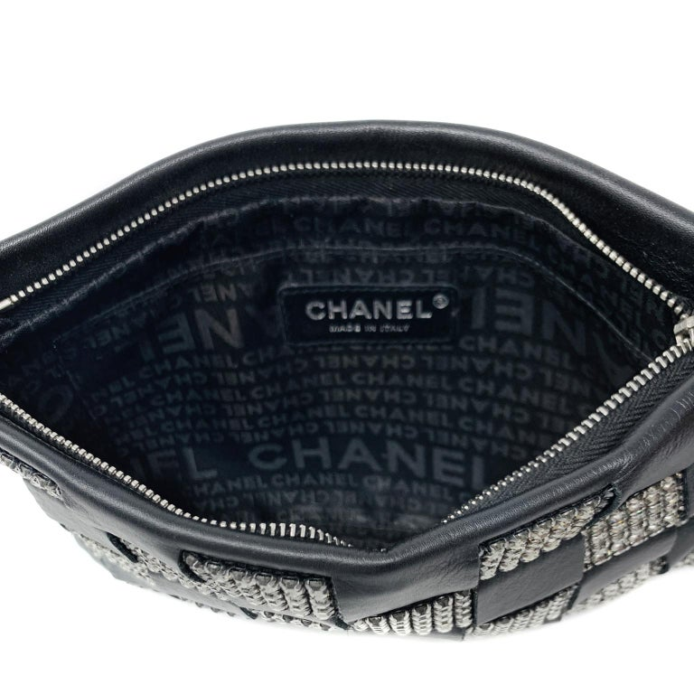 This authentic Chanel Black Lambskin and Crystal Wristlet is in pristine condition.  Perfectly sized for an evening's essentials, this pouch goes with everything. Black lambskin is woven in a checkered pattern with Swarovski crystals.  Zippered top