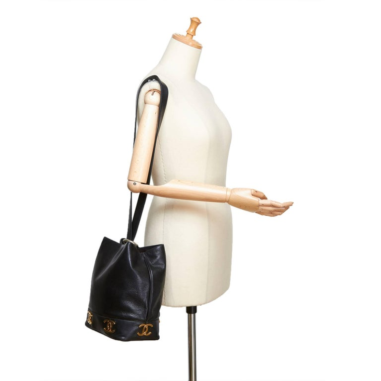 - Vintage 90s Chanel black lambskin leather bucket bag.     - Featuring single strap with a gold-toned