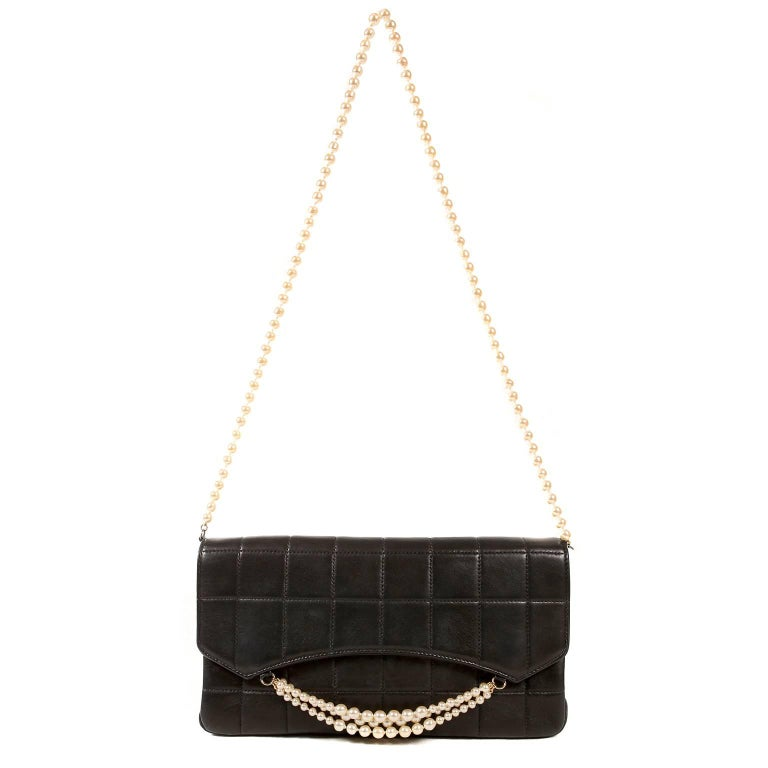 Chanel Black Leather and Pearl Shoulder Bag- Pristine Condition Elegant and feminine, the runway piece is truly a must have for any collector.  Black leather is quilted in square pattern.  Three strands of pearls drape across the front flap.