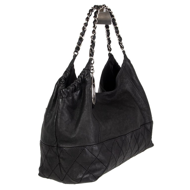 100% authentic Chanel 'Coco Cabas' tote shoulder bag in black grained calfskin featuring silver-tone hardware and chain shoulder straps. Opens with a magnetic button on top and is lined in black satin with one zipper pocket against the back and two