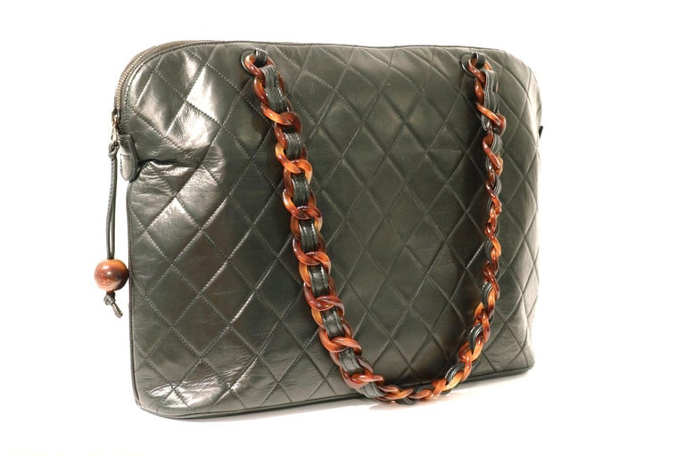 This authentic Chanel Black Leather Tortoise Chain Tote is in excellent vintage condition.  A beautiful piece for any collection that is certain to be enjoyed year-round. Black leather roomy tote is quilted in signature Chanel diamond pattern.