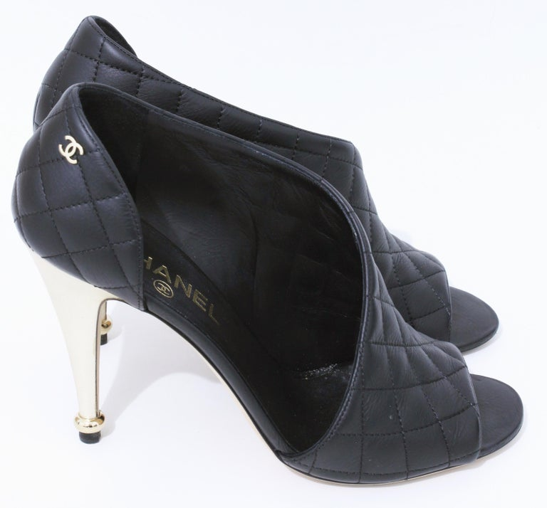 Lovely black calfskin open booties by Chanel from the 15C collection.  Feature gold colored heels and the CC logo at the outside corner of each shoe.  In very good preowned condition, we note some wear to the soles.  Come with an extra set of Chanel